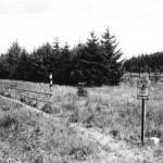 Grenzverlauf durch Schilder, neue Grenzsteine und eine Holzbarriere vor der auf DDR-Gebiet stehenden Grenzsäule gekennzeichnet.